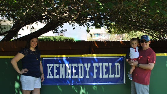 Lizette (left) and Ryan Kennedy with their son, Luke, stand by the outfield wall of the baseball field the family built for Luke's first birthday.