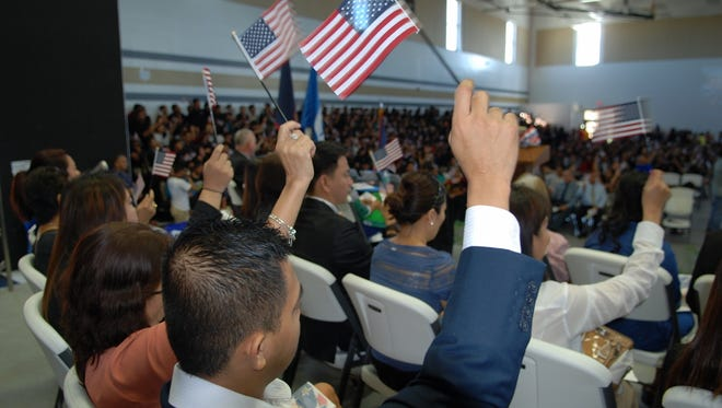 In this September 2016 file photo, new U.S. citizens wave American flags at Tiyan High School, where a special naturalization ceremony was held by the U.S. District Court of Guam.