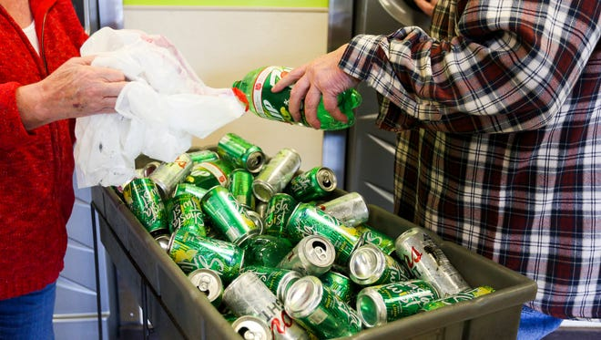 Wanda and George Stephenson begin loading cans and bottles at the BottleDrop Redemption Center on 4815 Commercial St. SE on Tuesday, March 21, 2017, in Salem, Ore. The two said it had been a while since they came in, and had several bags to drop off.