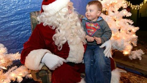 A child visits with Santa at Heritage Park last year. This year's Christmas event at the park will feature a new light show set to music and Santa's Village.