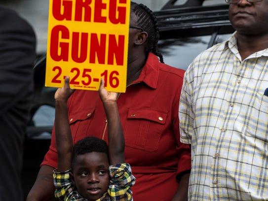 Kevon Jones, 5, holds a sign for Greg Gunn during a