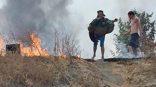 A woman throws her possessions down a hill Saturday afternoon after a fire burned through part of a homeless campsite on the north bank of the St. Johns River, just north of Visalia.