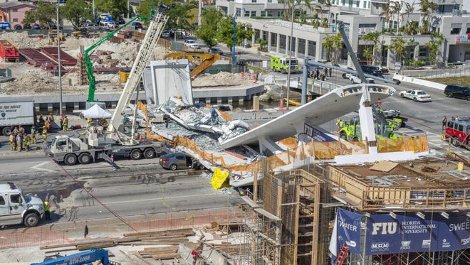 Emergency personnel work on a collapsed pedestrian bridge on the Florida International University in Miami.