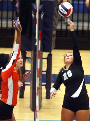 Siegel's Kristin Demonbreun (20) hits the ball over the net as Blackman players Paz Dozier Nnamah (4) front and Maddie Lee (31) back, during the Region 4-AAA volleyball Championship against Blackman, on Tuesday, Oct. 13, 2015, at Siegel.