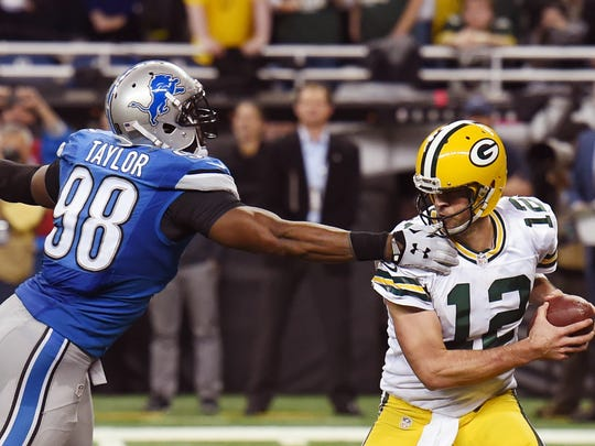 Detroit Lions defensive end Devin Taylor (98) reaches in on Green Bay Packers quarterback Aaron Rodgers (12) and is called for a face mask during the second half of an NFL football game, Thursday, Dec. 3, 2015, in Detroit.