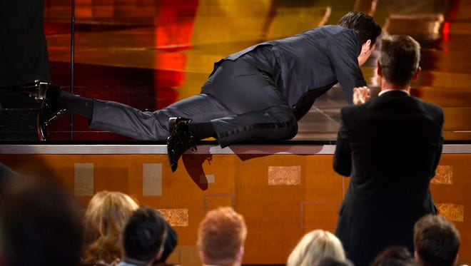 """Jon Hamm crawls on stage to accept the award for outstanding lead actor in a drama series for """"Mad Men"""" at the 67th Primetime Emmy Awards on Sunday, Sept. 20, 2015, at the Microsoft Theater in Los Angeles."""