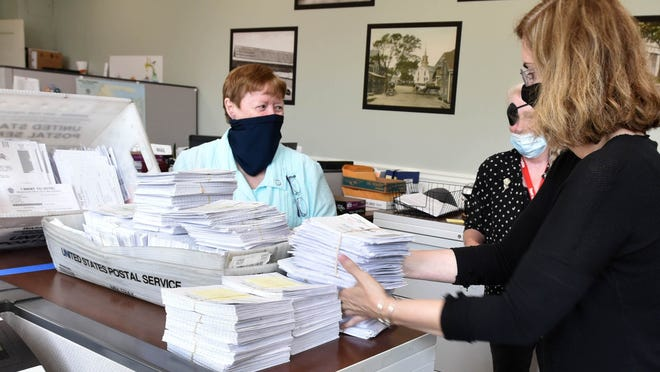 Applications for mail-in ballots have been piling up at local town clerk offices since the summer. Here, Barnstable Town Clerk Ann Quirk looks on as Janet Murphy, right, brings in another pile to add to a growing stack of applications.