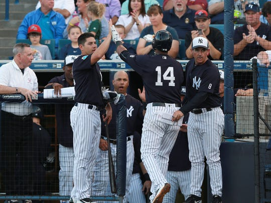 New York Yankees shortstop Starlin Castro (14) is congratulated by teammates after hitting a two-run home run during the second inning against the Toronto Blue Jays  at George M. Steinbrenner Field in Tampa Wednesday. Comcast has dropped the YES Network, which carries most Yankees games, from its lineup.
