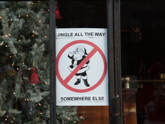 A sign in the window of a bar prohibits Santas during