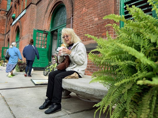 Doreen Goodling of York City sits on a custom bench while eating lunch outside Central Market on Thursday. York City Council is deliberating reauthorization of a special tax that benefits the Central Business District.
