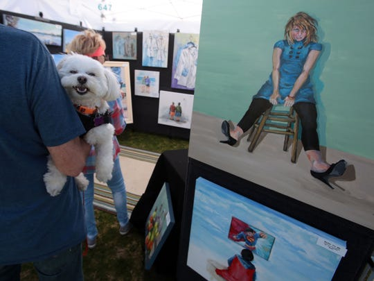 Bear and his owners Carol and Bill Baker of La Quinta enjoy paintings by Judy Mandel, of La Quinta, on Saturday, January 30, 2016 during the Southwest Arts Festival in Indio.