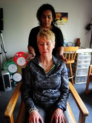 Beatrice Rodriguez performs Reiki on Ronda Wilson at Shiatsu Wellness Center.