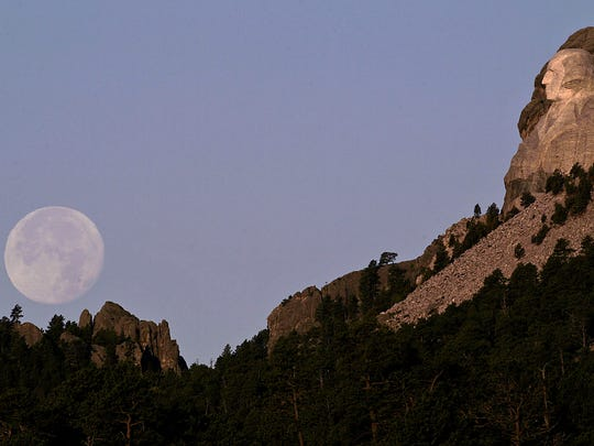 In this July 22, 2005 file photo, the freshly cleaned faces of South Dakota's Mount Rushmore National Memorial bask in the early morning sun as the moon sets in the distance.