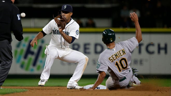 Seattle Mariners shortstop Ketel Marte, left, makes the catch to get Oakland Athletics' Marcus Semien out at as he tries to steal second base in the eighth inning of a baseball game, Saturday, Oct. 3, 2015, in Seattle.