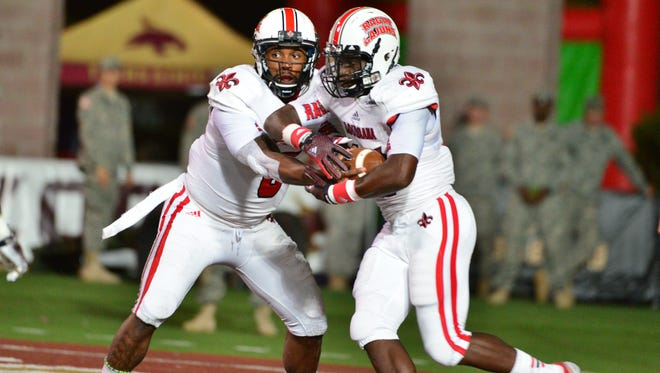 UL quarterback Terrance Broadway hands the ball off to running back Elijah McGuire in the first half of a 2014 game between the Ragin' Cajuns and Texas State.