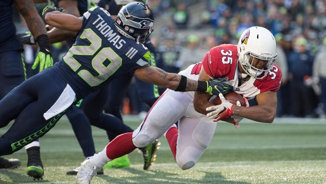 Dec 31, 2017; Seattle, WA, USA; Arizona Cardinals running back Elijhaa Penny (35) scores a touchdown as he gets past Seattle Seahawks free safety Earl Thomas (29) during the first half at CenturyLink Field. Mandatory Credit: Troy Wayrynen-USA TODAY Sports