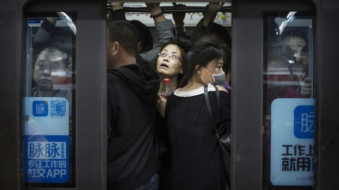 Chinese commuters crowd onto a subway car on the metro during rush hour on October 16, 2014 in Beijing, China.