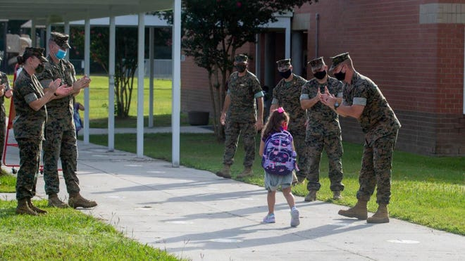U.S. Marines with 10th Marine Regiment, 2d Marine Division, welcome back students at Johnson Primary School aboard Camp Lejeune on Aug. 24. The Marines cheered for students as they arrived for the first day of school, all while adhering to COVID-19 guidelines.