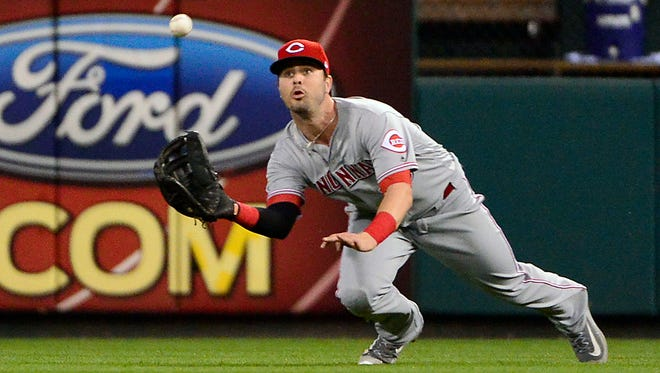 Cincinnati Reds right fielder Jesse Winker (33) dives and catches a fly ball hit by St. Louis Cardinals catcher Yadier Molina (not pictured) during the first inning at Busch Stadium.