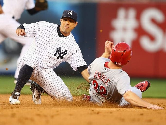 Yankees second baseman Brian Roberts tags out Cincinnati Reds right fielder Jay Bruce attempting to steal second base during the second inning at Yankee Stadium