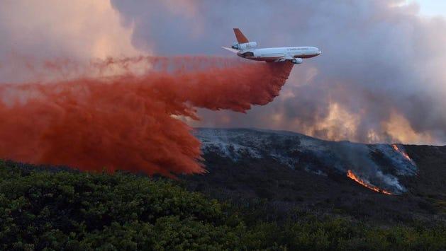 An airplane drops fire retardant on a blaze near Vandenberg Air Force Base on Thursday.