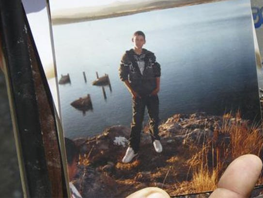An unidentified relative shows a photo of Sergio Adrián