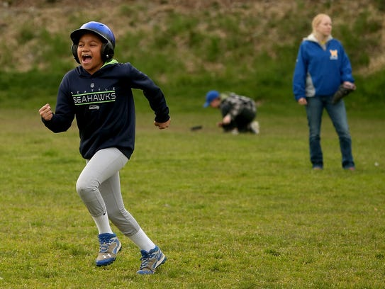 Jay Littleraven-Oliver, 12, gives a yell as he runs to third during practice at the Warren Avenue Playfield on Tuesday. Generations of Bremerton children have played baseball and football at the field, which is in dire need of improvements.