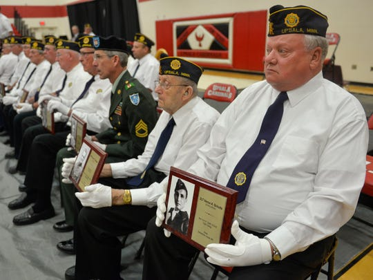 Members of Upsala American Legion Post 350 hold plaques Monday, May 30,  honoring military members from the area who died. The Memorial Day ceremony took place at Upsala High School.