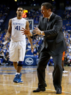 Kentucky head coach John Calipari, right, shows forward Trey Lyles what to do when he catches the ball during a break in the action. 