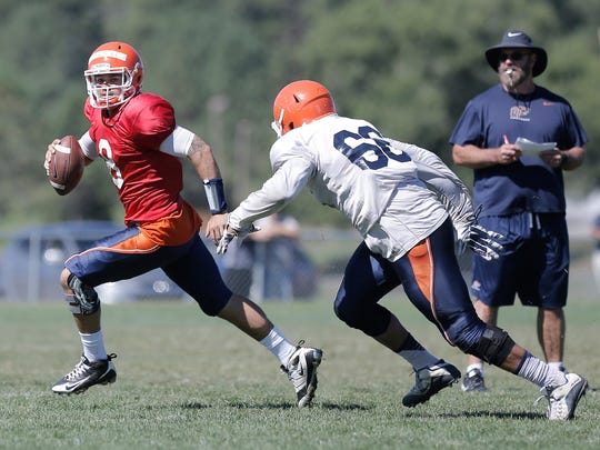 UTEP quarterback Zack Greenlee scrambles away from defensive lineaman Christian Harper as he looks for a receiver down field Friday at Camp Ruidoso. Head coach Sean Kugler, right, says he's waiting for one quarterback to emerge as the leader before deciding on his starter.