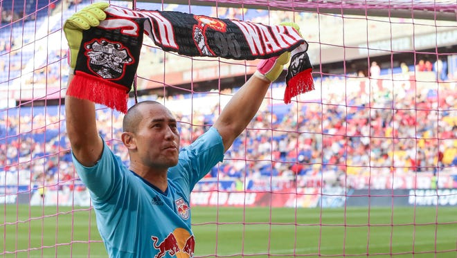 New York Red Bulls goalkeeper Luis Robles raises a scarf to salute the fans at Red Bull Arena.