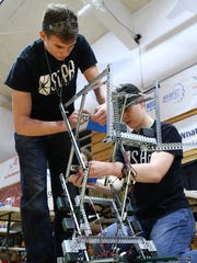 Tanner Lacroix, left, and Cameron Cox of Shasta Charter Academy work on their team's robot to get ready for Saturday's robotic competition. The Shasta Charter Academy team was one of three teams that advanced to statewide competition.