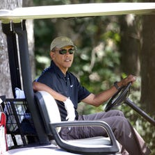 President Barack Obama sits in a golf cart while golfing Thursday at Farm Neck Golf Club, in Oak Bluffs, Mass.