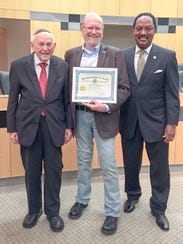 Jerry Donnellan, center, holds certificate standing