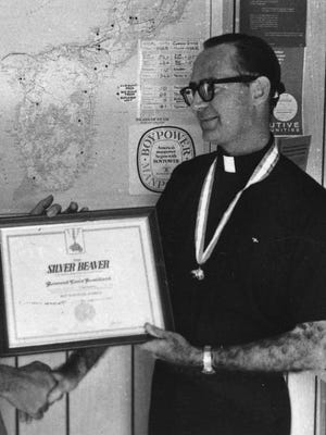 Father Louis Brouillard is shown in this undated Pacific Daily News file photo receiving a Silver Beaver award for his scouting hierarchy from a Navy captain.