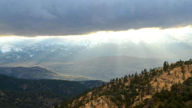 Light filters through storm clouds over a valley area seen from Nevada 341 near Virginia City on April 11, 2017.