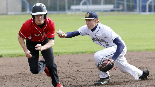 Notre Dame shortstop Matt Smith reaches out to tag Brett Stewart of Newark Valley after a run down during Wednesday's IAC game in Southport.