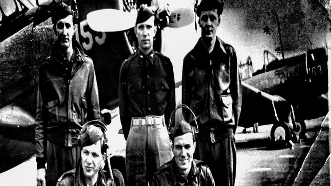 Captain Robert Bender poses with a crew in front of an airplane (not his own). He is in the back row at left.