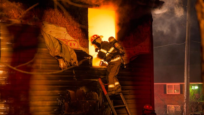 Augusta County firefighter P.J. Sibold, as identified by the name on his jacket, tries to subdue glowing flames before entering the second-floor window of an apartment building that caught fire in Staunton on Thursday, Jan. 8, 2015.