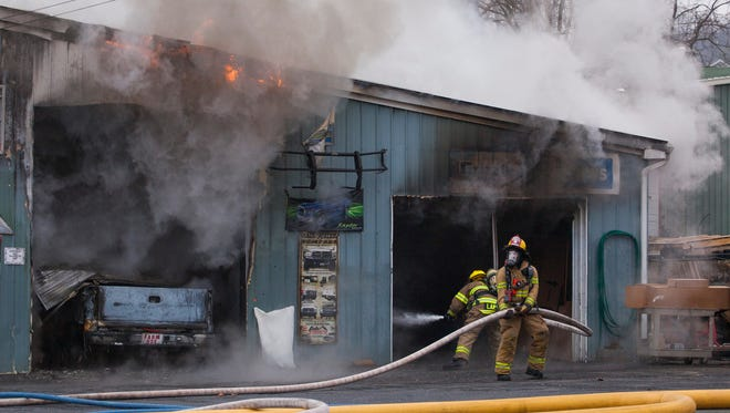 Augusta County firefighters battle a blaze inside the garage of Mountain Valley Truck and Trailer in Staunton on Tuesday, Jan. 13, 2015.