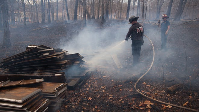 Staunton firefighters work to contain a brush fire that started along the east-west railroad track in Augusta County on Thursday, March 26, 2015. As many as seven brush fires were counted along the rail line.