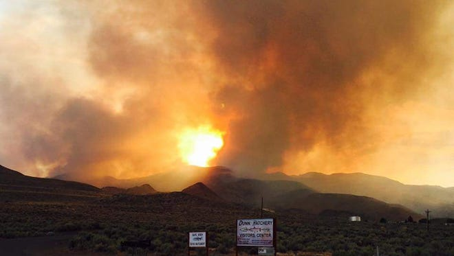 Smoke and flames are visible Friday from a wildfire burning in Sutcliffe, about 35 miles north of Reno. The wildfire was deterred Sunday from burning the tribal town that had evacuated hundreds of residents.