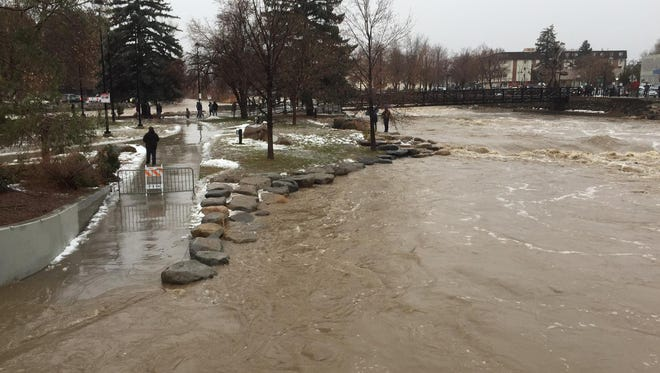 The Truckee River laps over the sidewalk in Wingfield Park in Reno on Sunday, Jan. 8, 2017, on its way to flood stage. The river is expected to crest early Monday, Jan. 9, 2017, in Sparks, Nev.