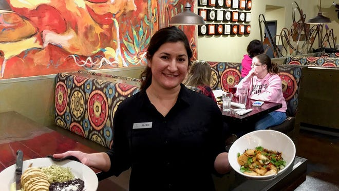 Server Alexis Allouche with dinner orders at Cicada Cantina in Redding.