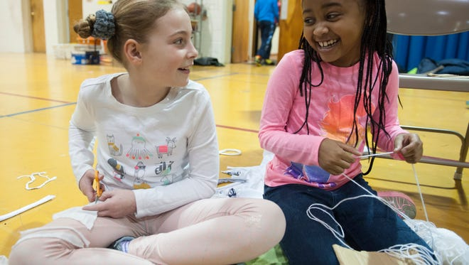 Friends School Mullica Hill students, Dealia Owens, left, and Neah Ellis share a laugh as the work together on a craft donation project in honor of Martin Luther King Jr.  They are making toys for animals at a Gloucester County animal shelter out of yarn cardboard and cotton that Dealia is cutting