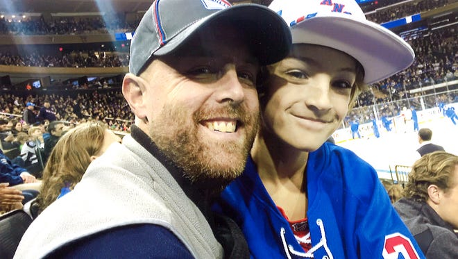 Jay Heverly poses with his son James at an ice hockey event.