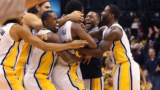 Indiana Pacers teammates swarm around Solomon Hill after he caught Rodney Stuckey's air ball under the basket and made a game-winning layup as the clock expired for the dramatic 88-86 win over the Charlotte Hornets at Bankers Life Fieldhouse in Indianapolis on Wednesday, Nov. 19, 2014.