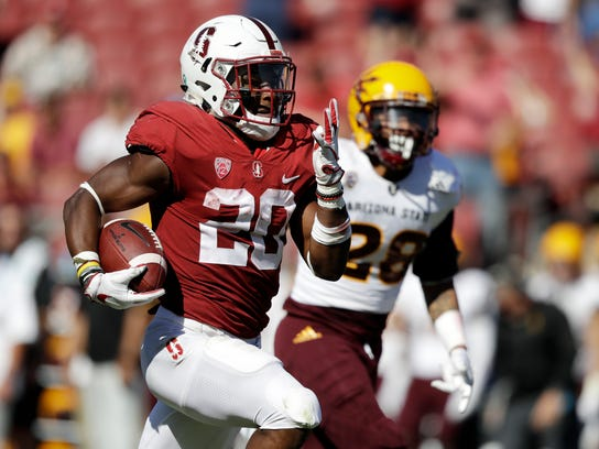 FILE - In this Sept. 30, 2017, file photo, Stanford running back Bryce Love, left, runs for a touchdown past Arizona State defensive back Demonte King (28) during the third quarter of an NCAA college football game in Stanford, Calif. Love established himself as a Heisman candidate early by rushing for 564 yards in back-to-back wins over UCLA and Arizona State. He kept adding to those numbers and leads all Power 5 running backs in yards rushing (1,973) yards per carry (8.3) and 100-yard games (11), and also set an FBS record with 12 runs of at least 50 yards. (AP Photo/Marcio Jose Sanchez, File)