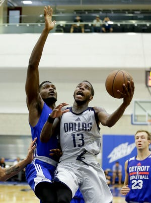 The Mavericks' Dwight Buycks  makes a shot after getting by the Pistons' Landry Nnoko during the second half of an NBA summer league game, Thursday, July 6, 2017, in Orlando.