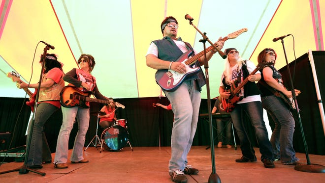 Andy Booher, center, a policy support representative with SECURA Insurance Co., performs a talent show act with fellow employees during the United Way Fox Cities Community Kickoff event Wednesday, August 26, 2015, at SECURA Insurance Co., in Appleton Wis. Dan Powers/Post-Crescent Media